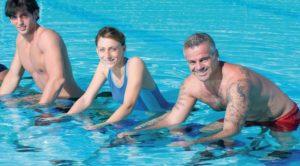 Trois personnes qui pédalent dans l'eau pratique de l'aquabiking