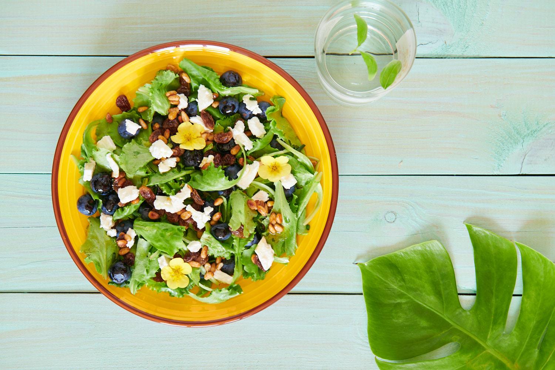 Photo d'un saladier rempli de salade verte, myrtilles, chèvre frais, pignons de pin caramélisés et raisins secs