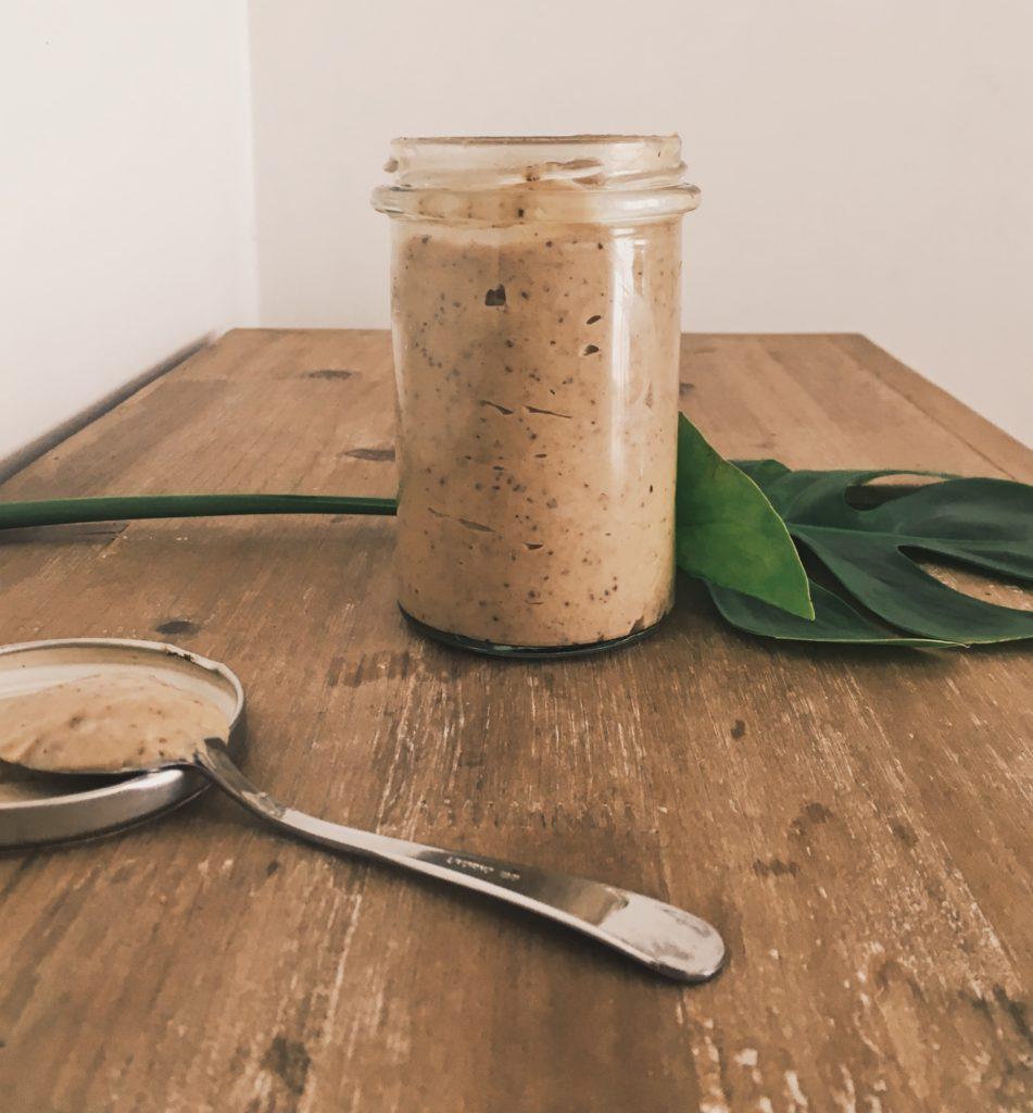 Pot en verre contenant du caramel de dattes au beurre de cacahuète et sirop d'érable