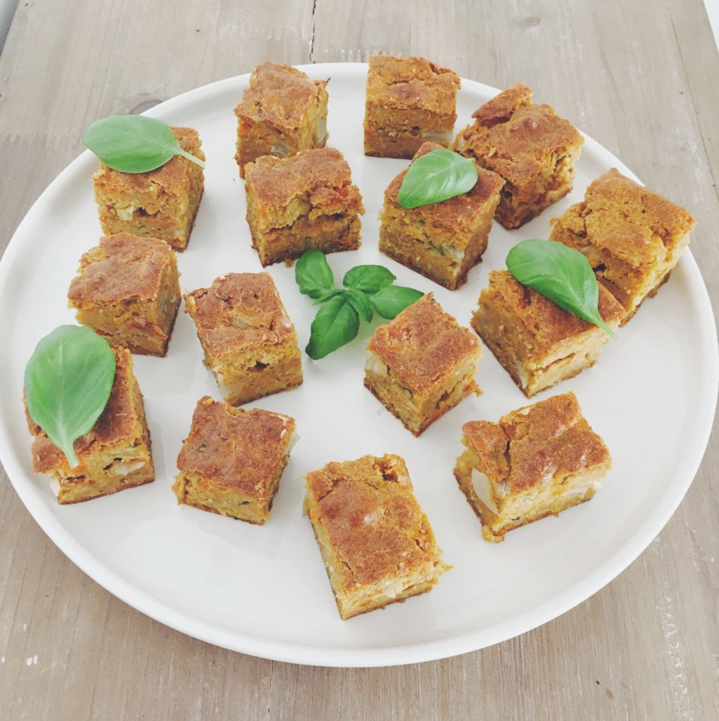 Assiette blanche de brownies aux carottes et feuilles de basilic