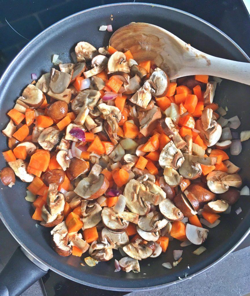 pôele contenant des champignons, carottes et oignons pour sauce bolognaise vegan