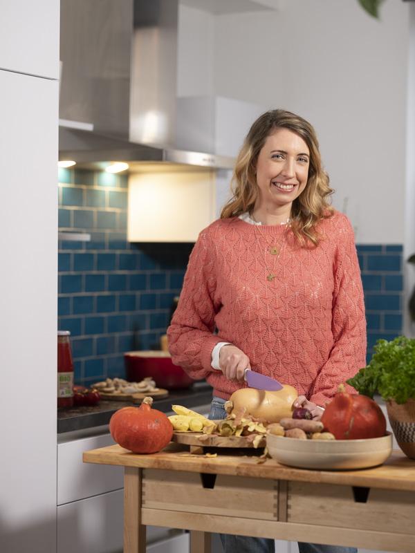 Jeune fille qui est en train de cuisiner un plat dans sa cuisine