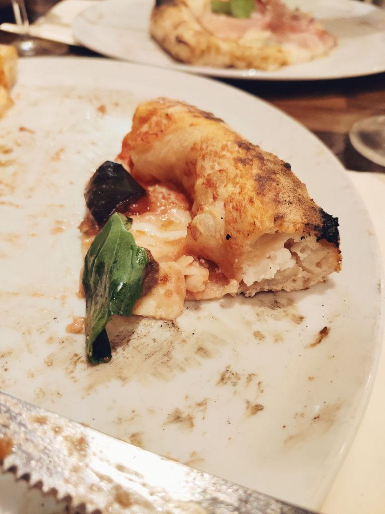Pizza avec croûte fourrée à la ricotta. Gros plan sur la de La Piola Pizza à Saint-Josse, Bruxelles. Pizza napolitaine.
