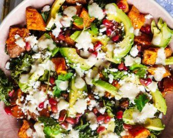 Photo d'un saladier contenant une salade de patate douce, des feuilles de chou kale, des tranches d'avocat, de la feta et des graines de grenade