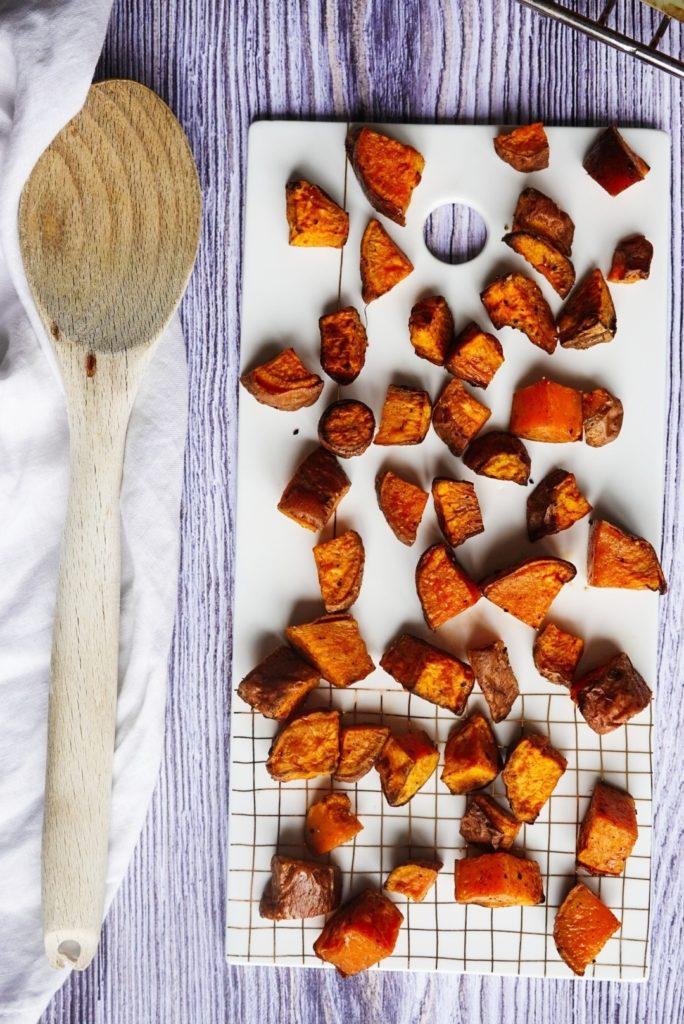 Photo de cubes de patate douce rôtis au four avec spatule en bois